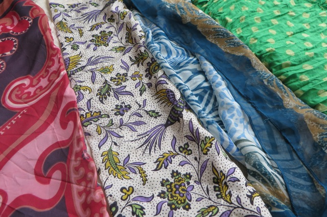 Four scarves in various colours and patterns