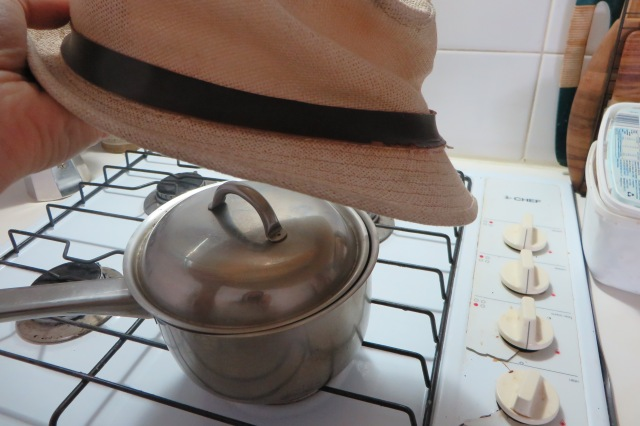 Reshaping hat with steam from saucepan on stove